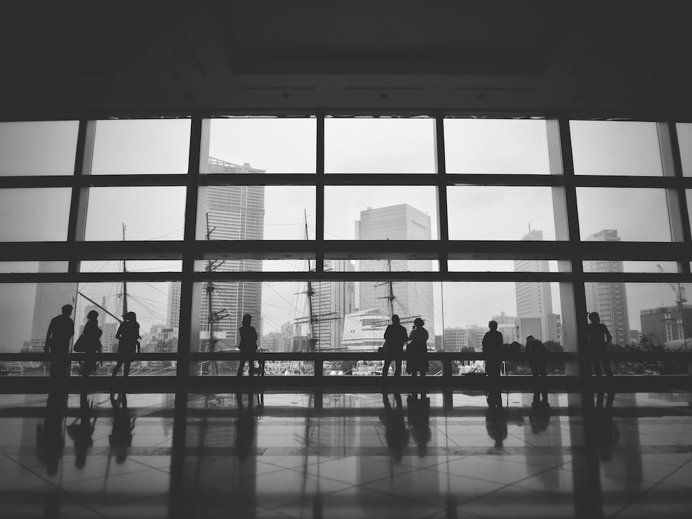 grayscale photography of people standing inside building near window