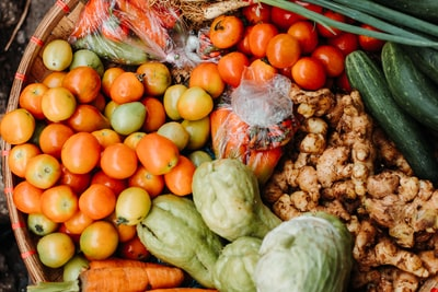 red and orange tomatoes near chayote and cucumbers leafy teams background