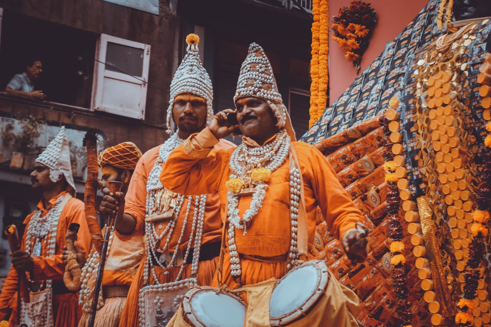 men in orange and white traditional dresses