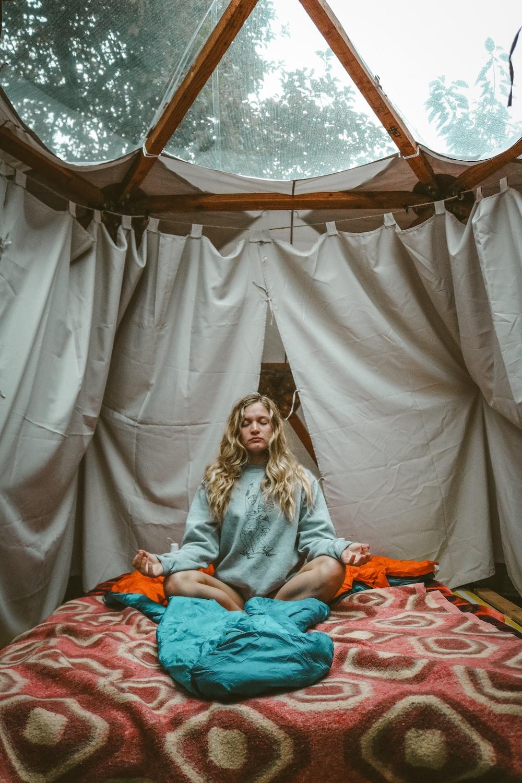 sitting woman on mattress inside room