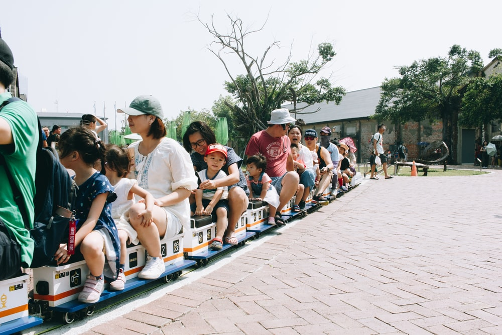people sitting on train ride near outdoor during daytime
