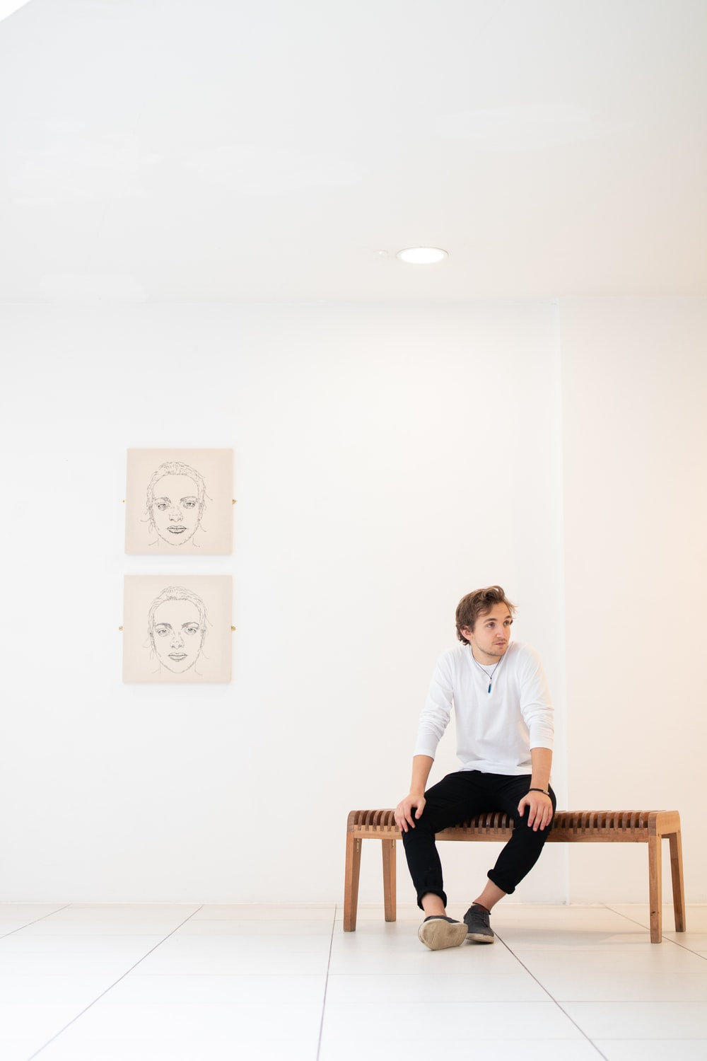 man in white shirt sitting on bench beside portraits