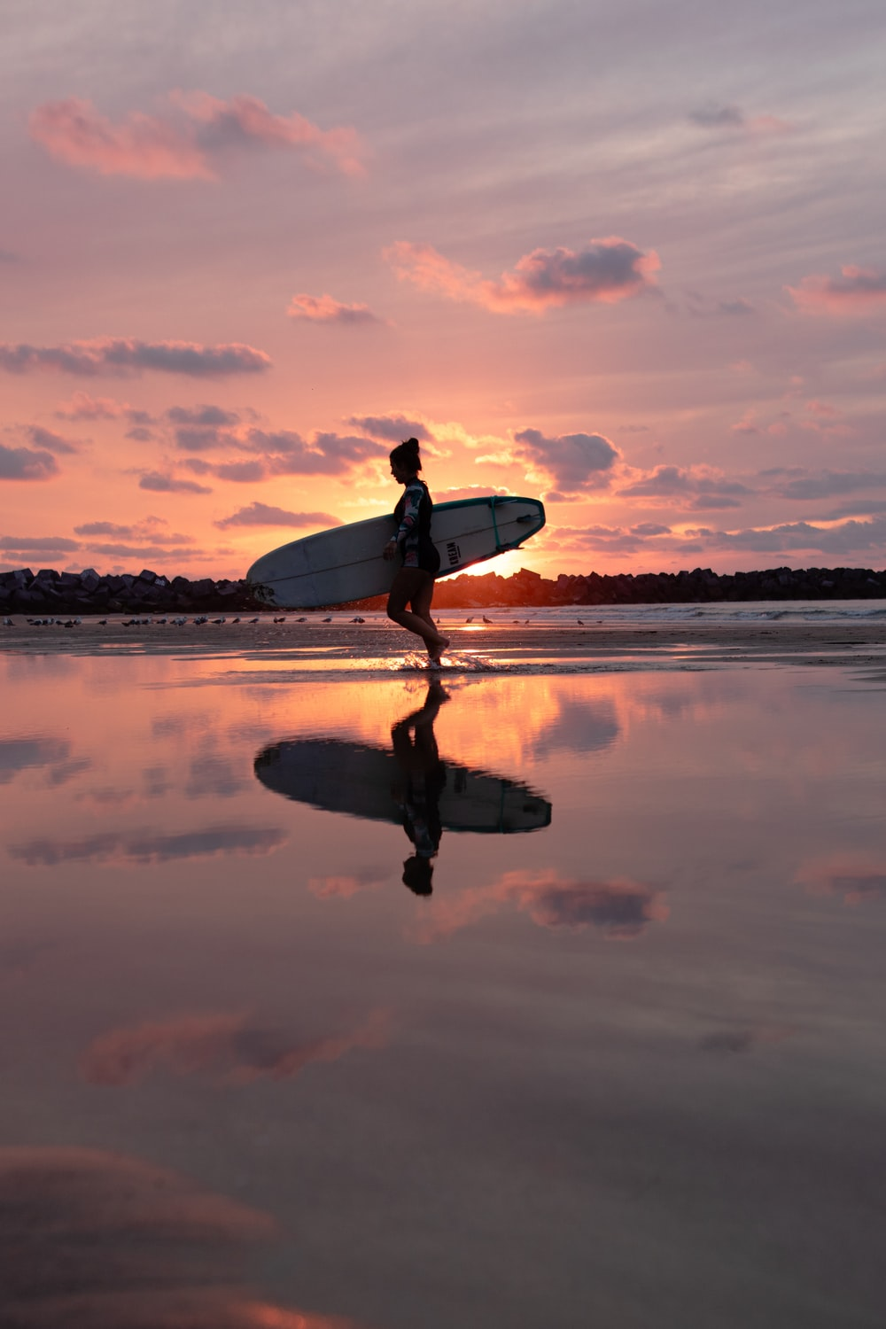 reflection of walking woman holding surfboard on body of water during golden hour