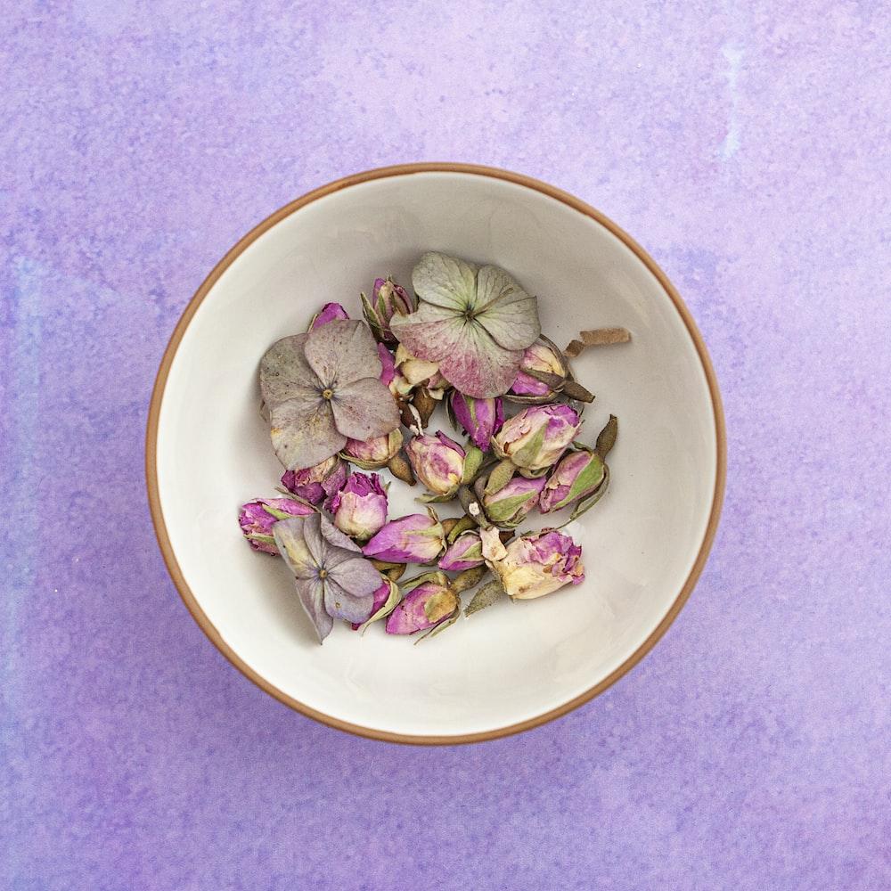 pink-petaled flower on white ceramic bowl