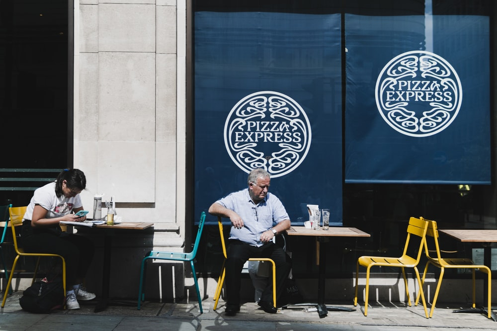 man sitting on chair outside building during daytime