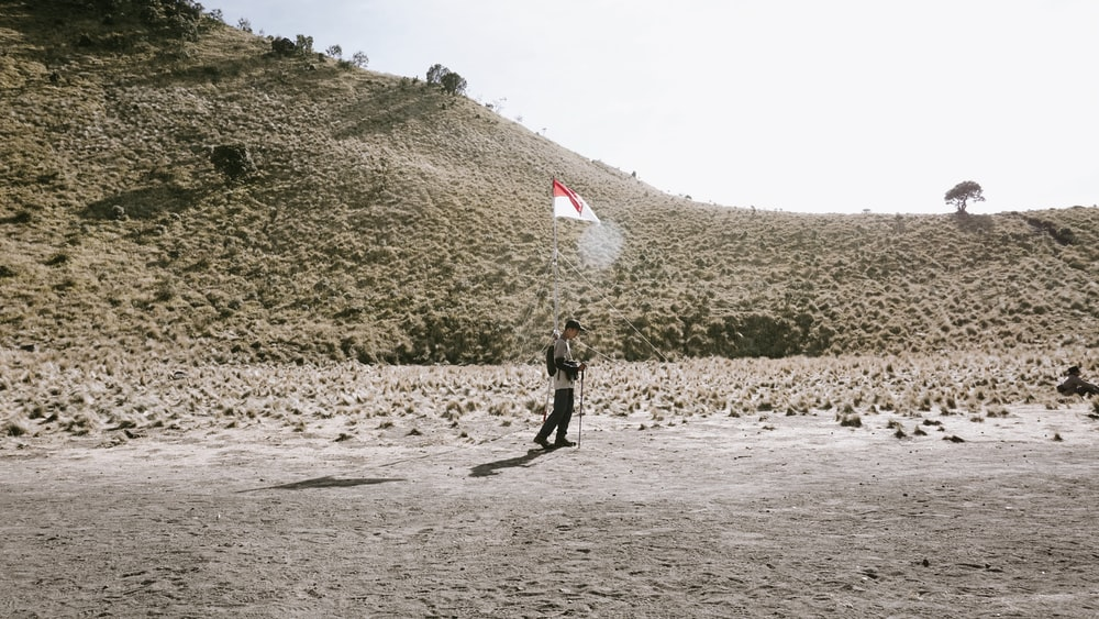 man holding white and red flag
