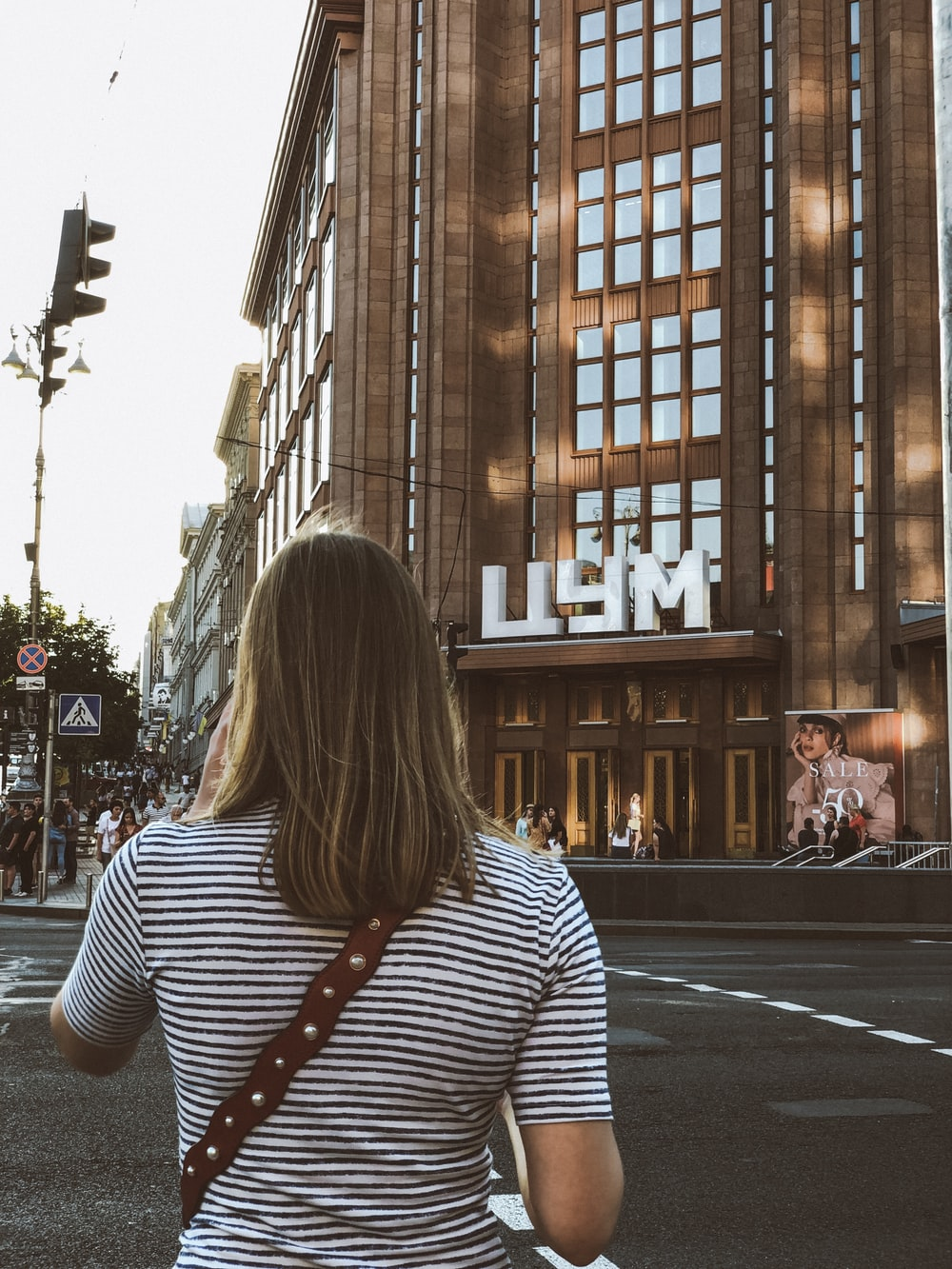 woman wearing black and white stripe shirt across LLYM building