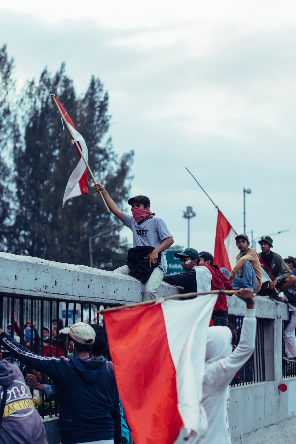 people holding white and red flag