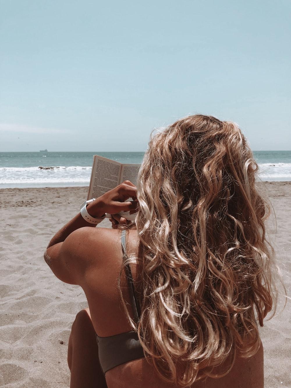 woman in brown bikini holding book