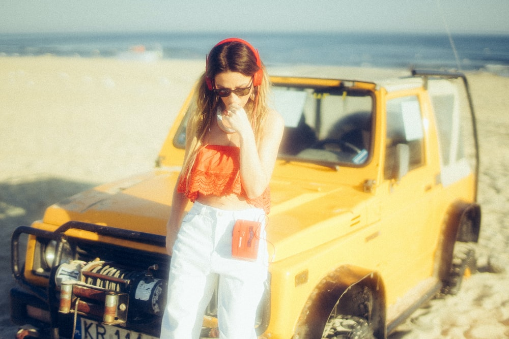 woman standing near yellow vehicle