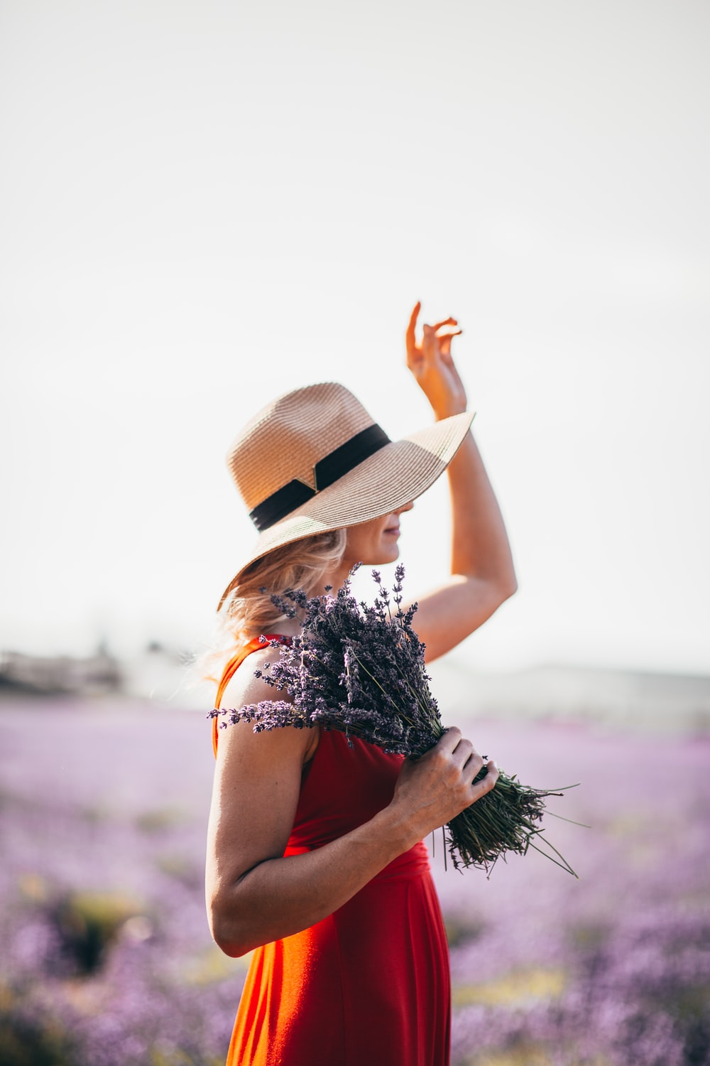 woman wearing red sleeveless dress holding lavender flowers