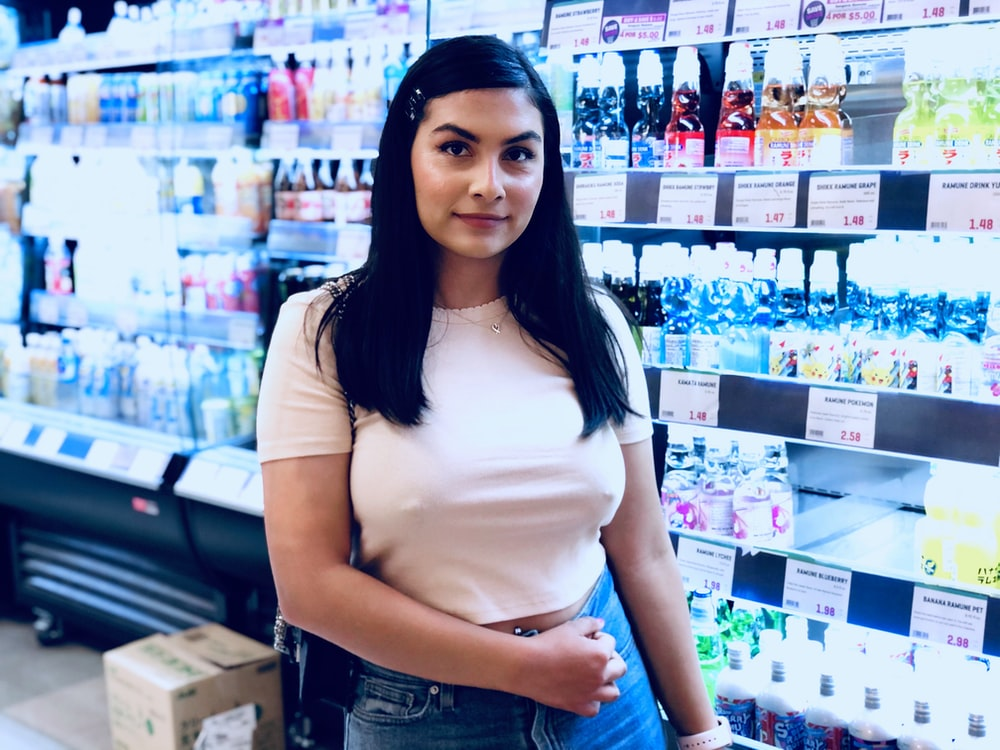 woman standing beside beverage displat