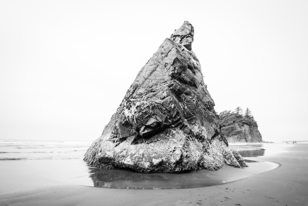grayscale photography of rock formation beside body of water