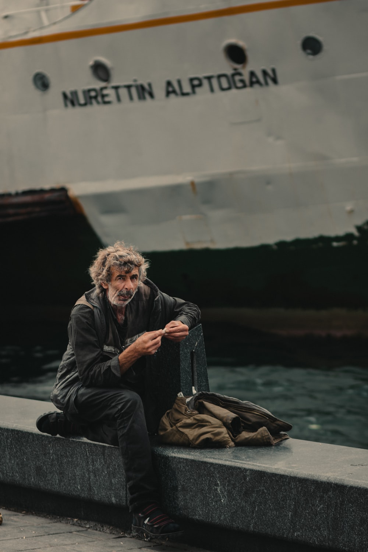 man sitting near sailing ship