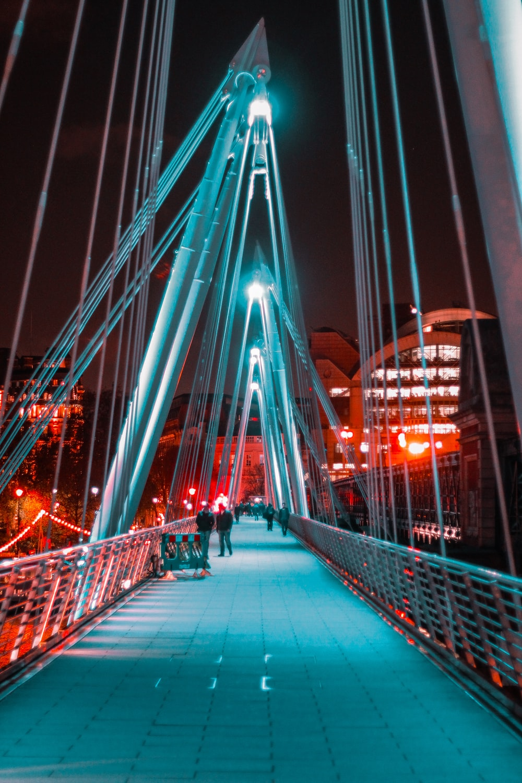 people on bridge during nighttime