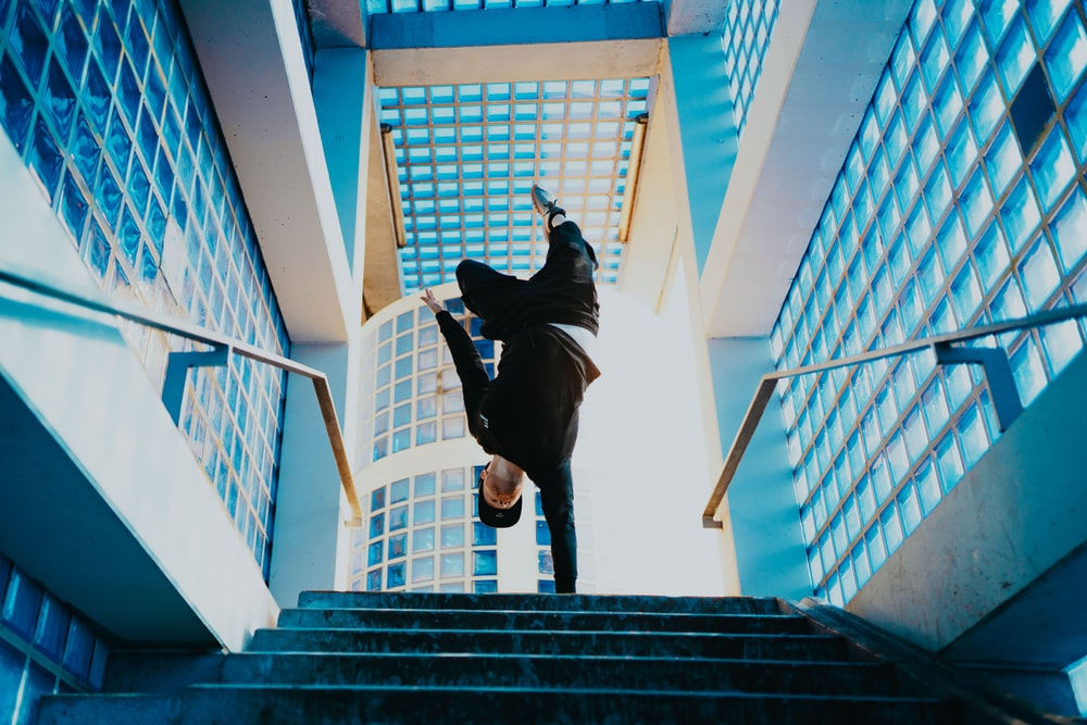 man balancing on one hand on top of the stairs during day