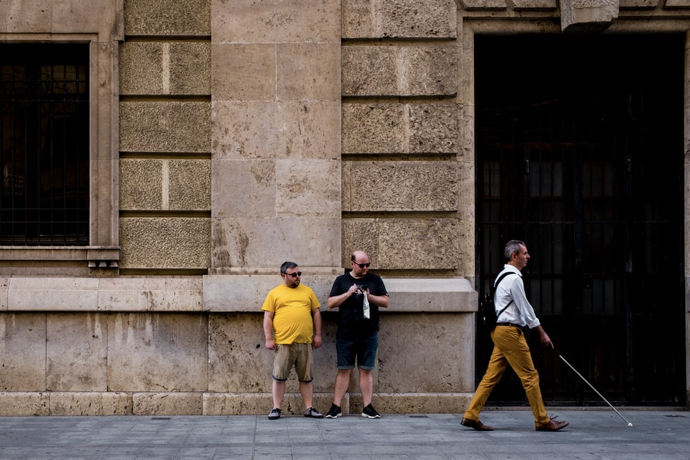 two men standing near wall and near man walking holding walking cane