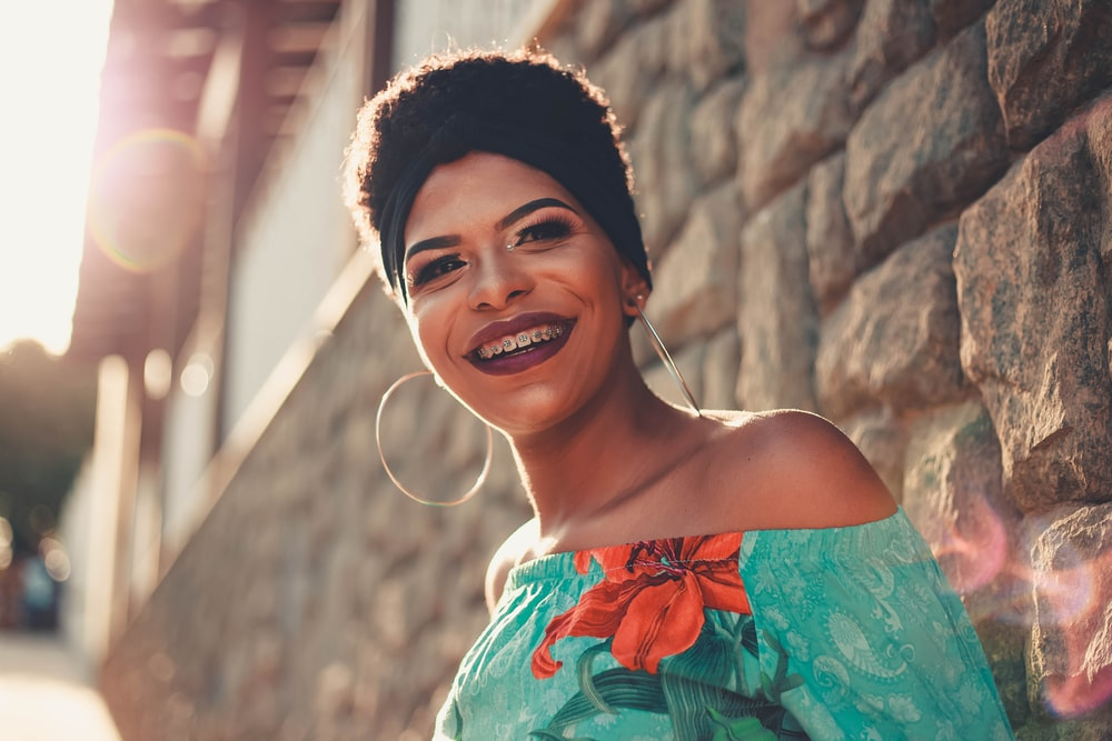 smiling woman leaning on brick wall