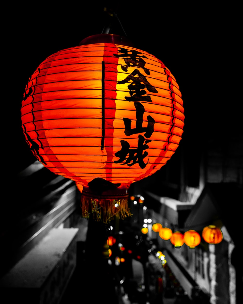 lighted orange and black paper Chinese lamps during night time