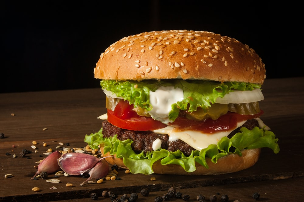 hamburger with vegetables on wooden surface