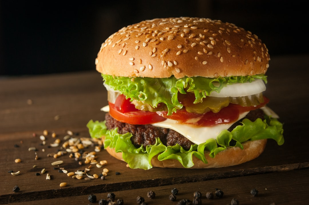 big burger on a wooden table with pepper and sesame
