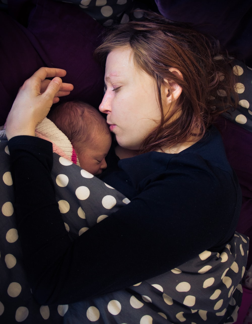 woman kissing on baby's forehead