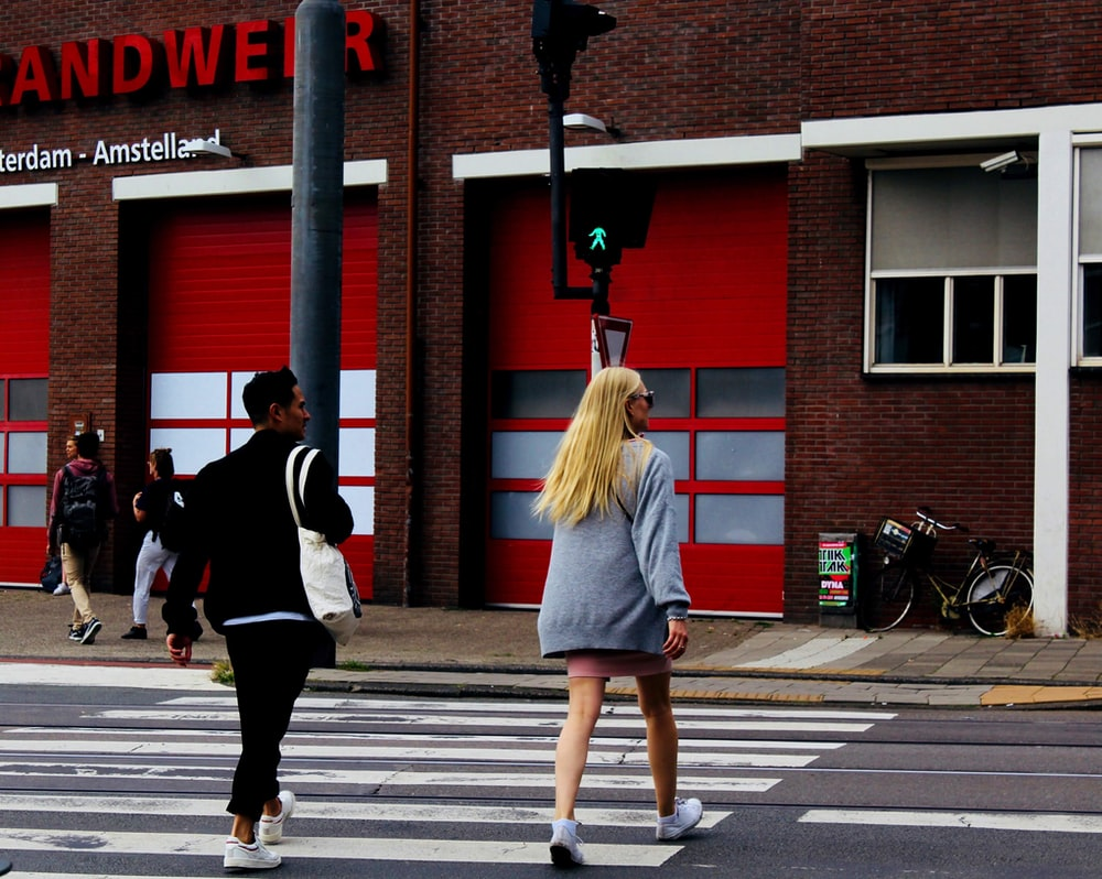man and woman walking near red building