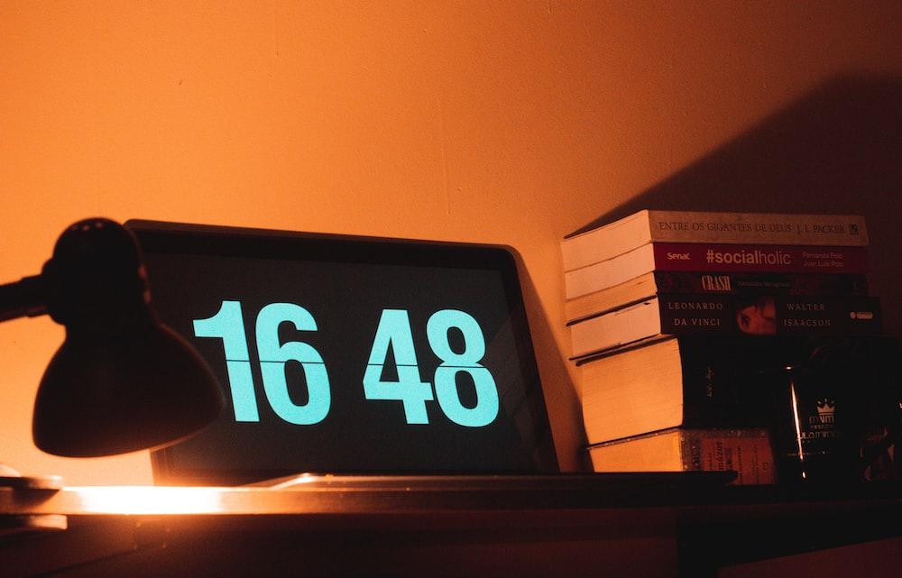 black digital clock reading at 16 48