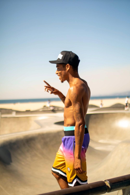 topless man on skateboard field