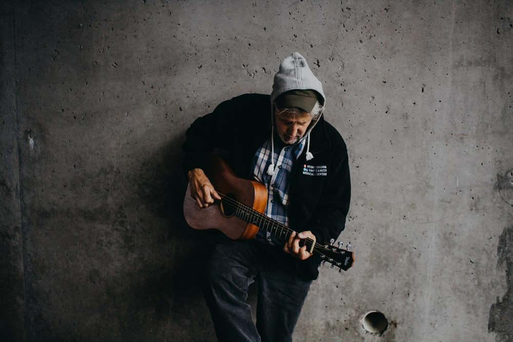 man lean on wall holding guitar
