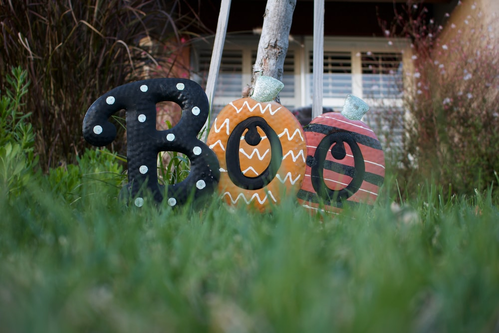 three assorted-color boo ornaments on grass