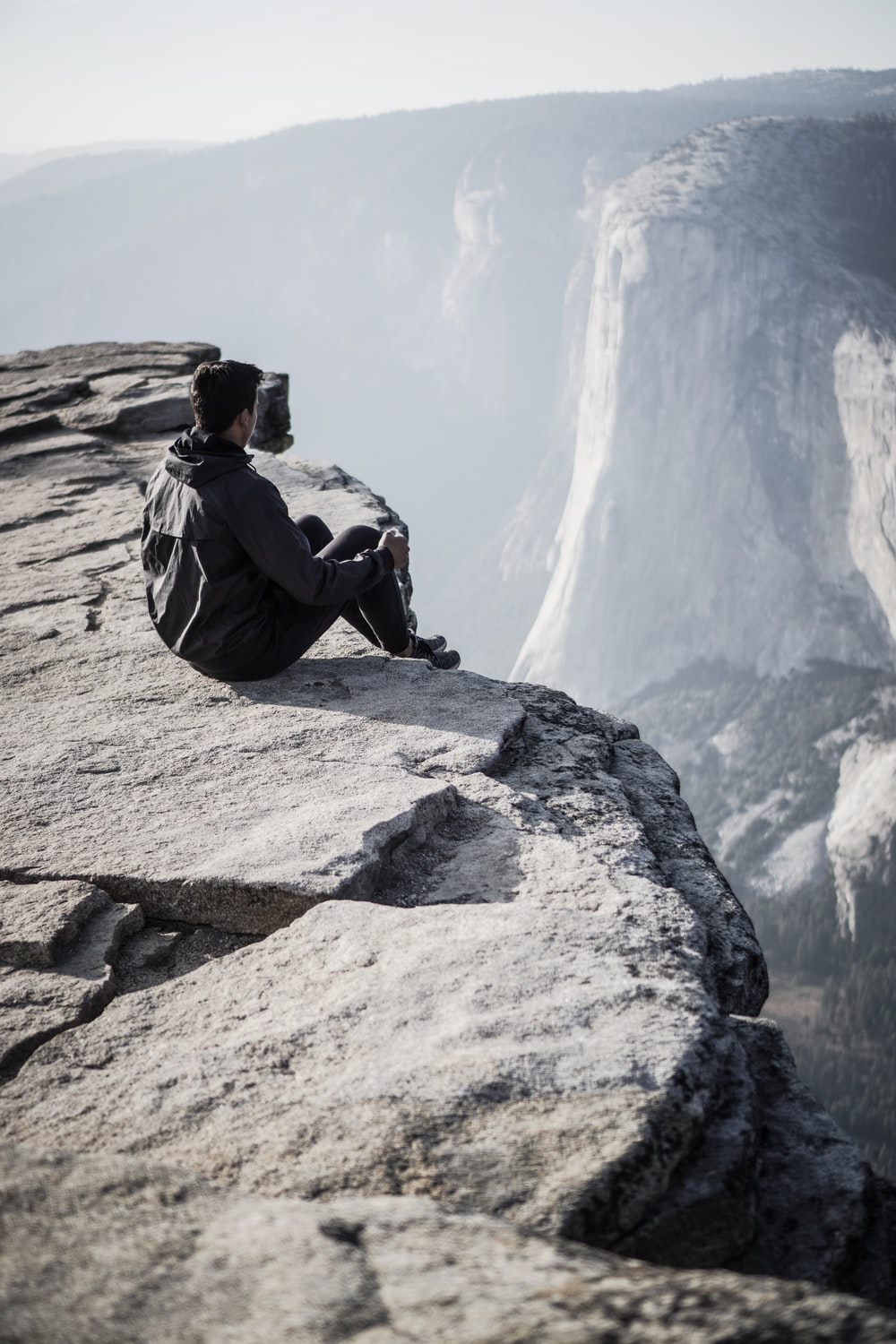 man sitting on rocky mountain cliff during day