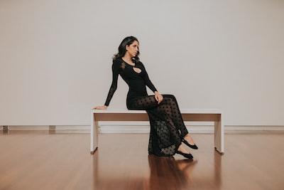 woman in black dress sitting on bench