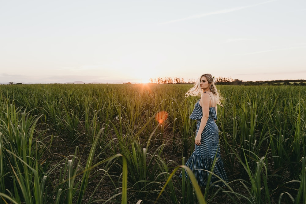 shallow focus photo of woman in blue spaghetti strap dress on grass field