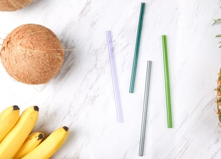 four assorted-color straws beside coconut, bananas, and pineapple