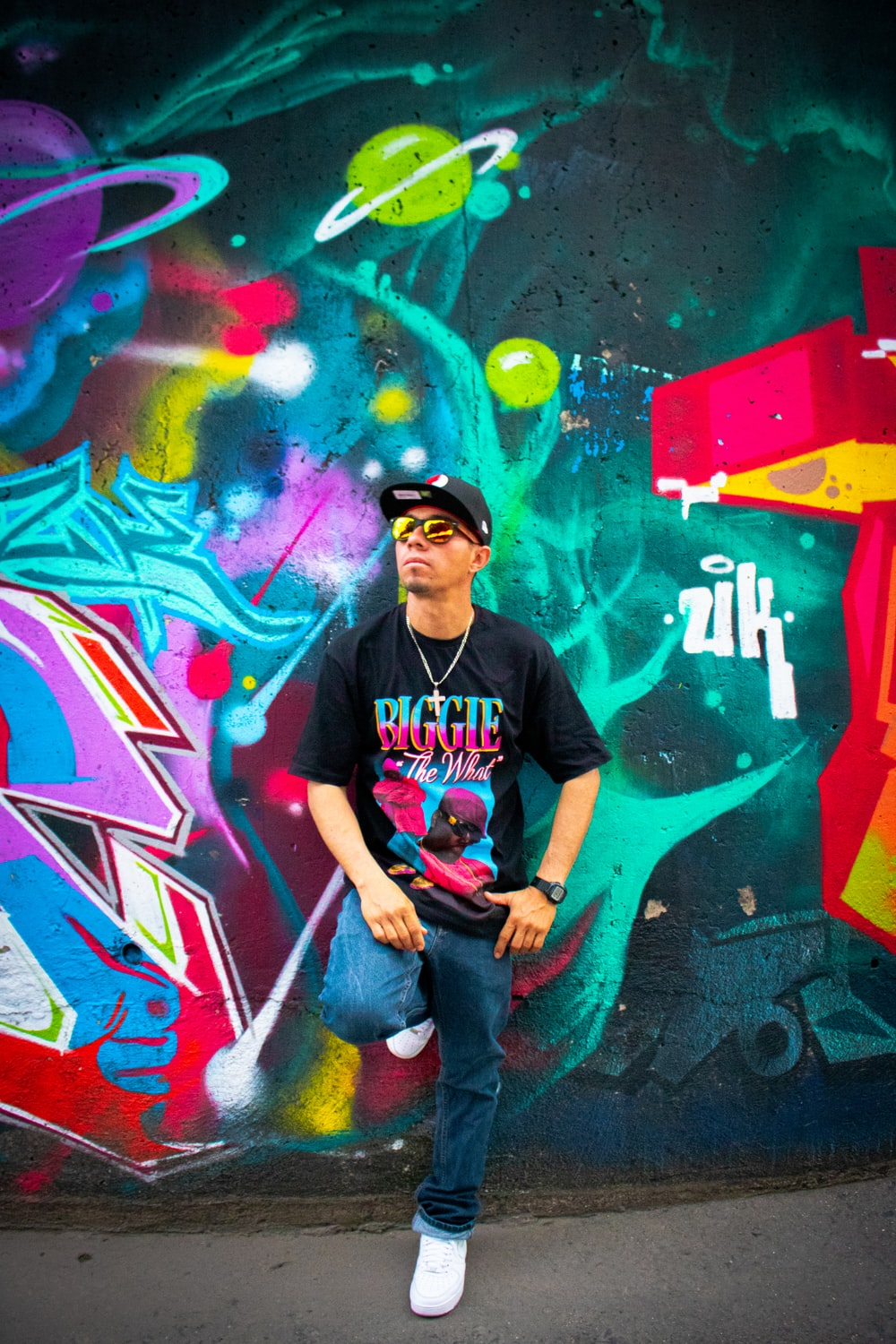man leaning on graffiti wall