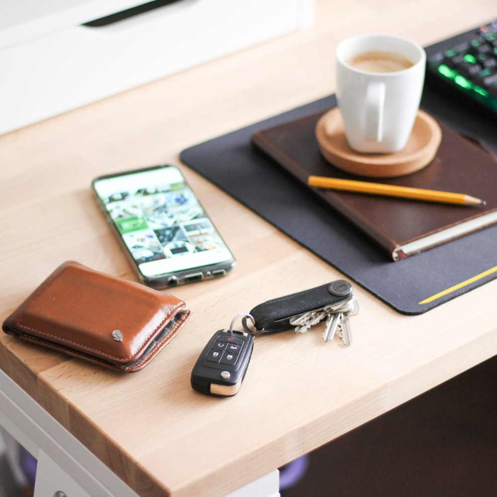 yellow wooden pencil on brown hardbound book near cappuccino, silver Android smartphone, brown leather bifold wallet, and black car fob
