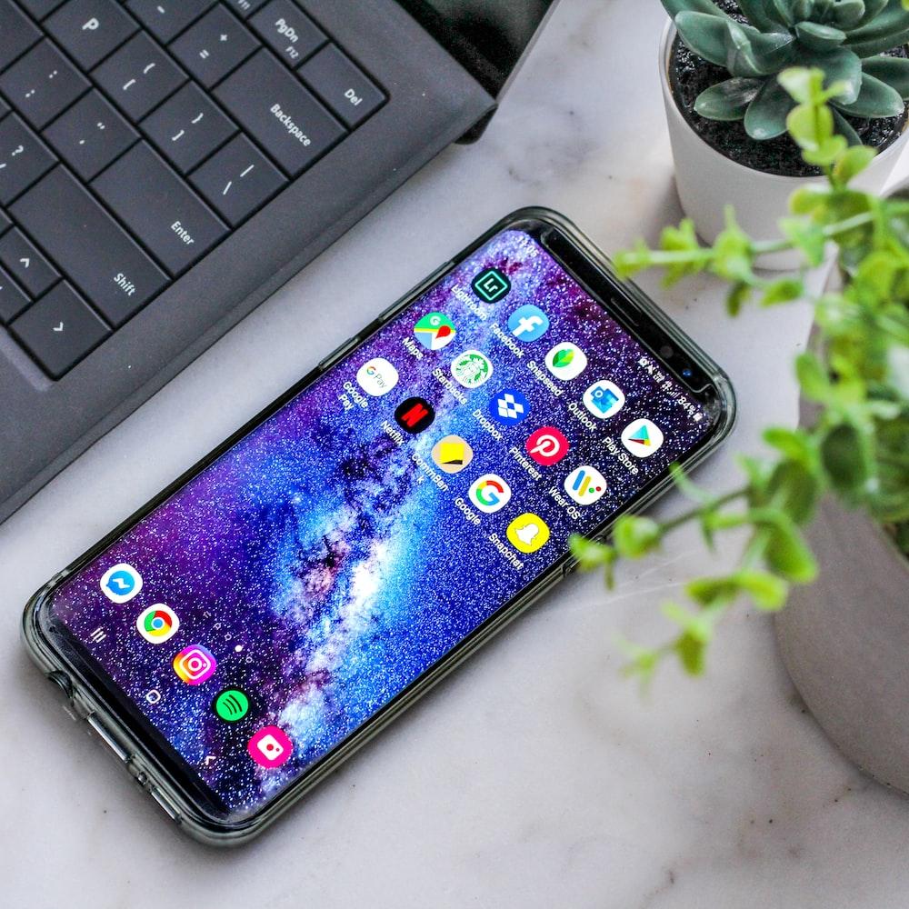 smartphone turned on beside laptop