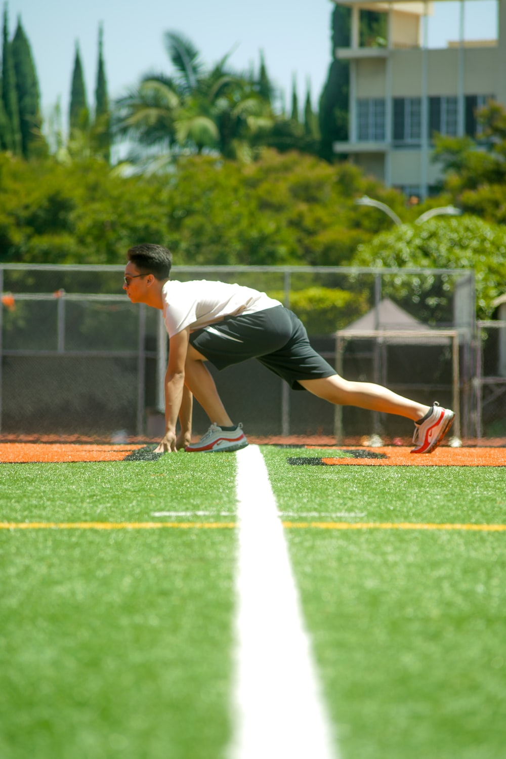 man on grass getting ready to run during day