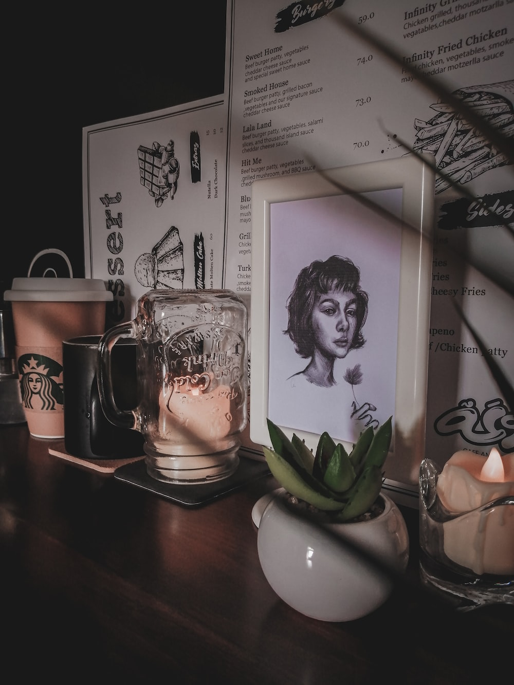 charcoal sketch of woman with frame near green succulent plant