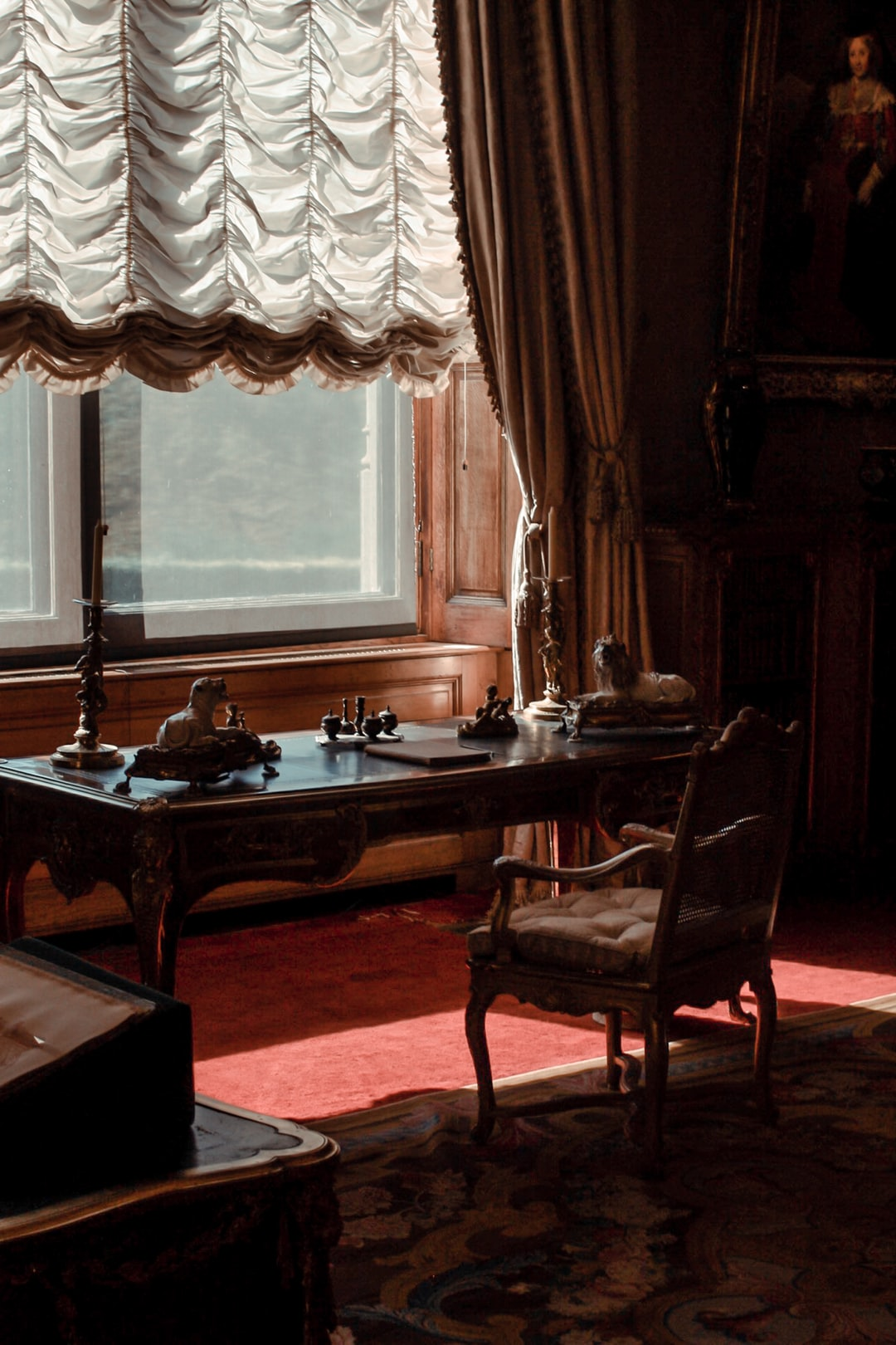 Antique furniture in manor house with lighting from the window and a desk, chair, rug and curtains