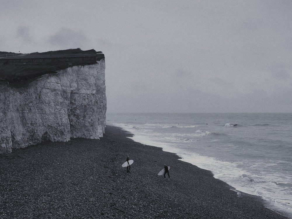 grayscale photography of two person holding surfboard walking near cliff and sea