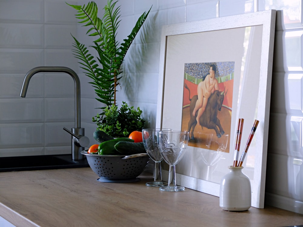 nude person riding bull painting in white frame beside wineglasses, vegetables, and plant