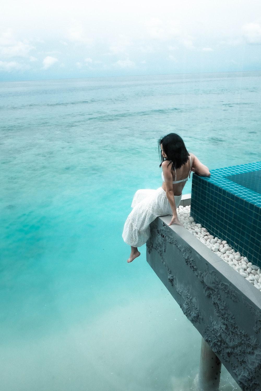woman sits near shore