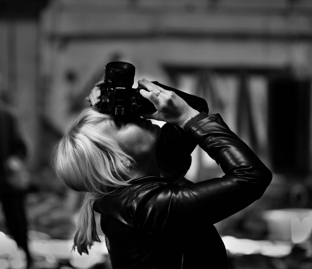grayscale photo of woman using camera