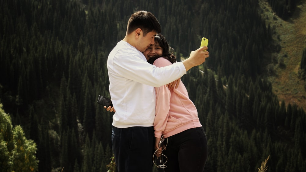 man hugging woman surrounded by trees