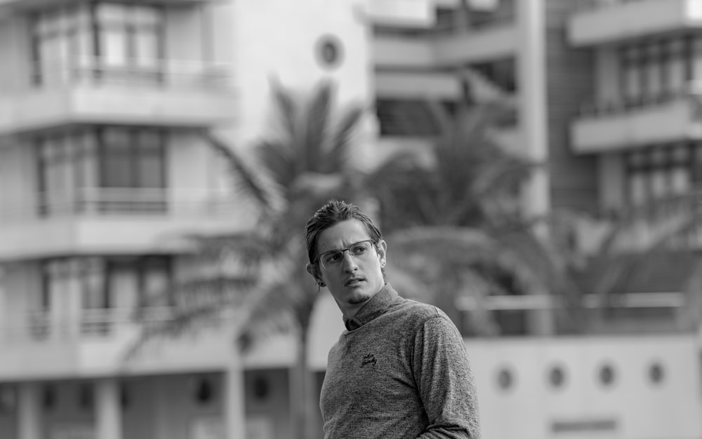 grayscale photo of man wearing long-sleeved top