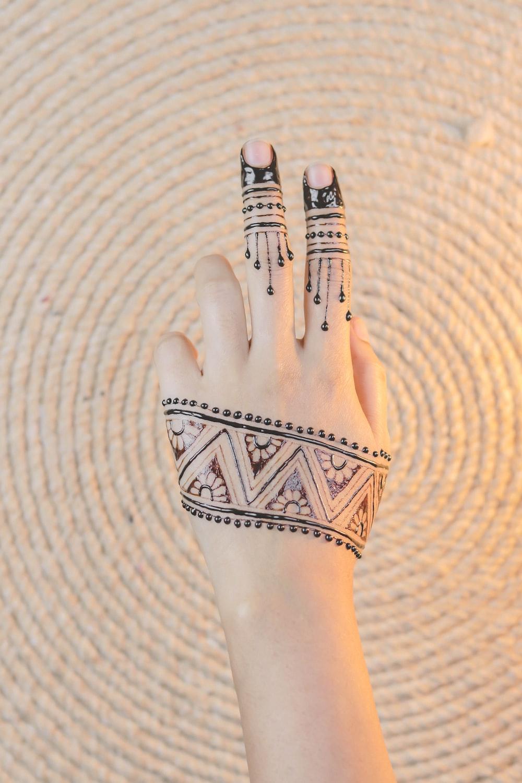 black henna covered left hand
