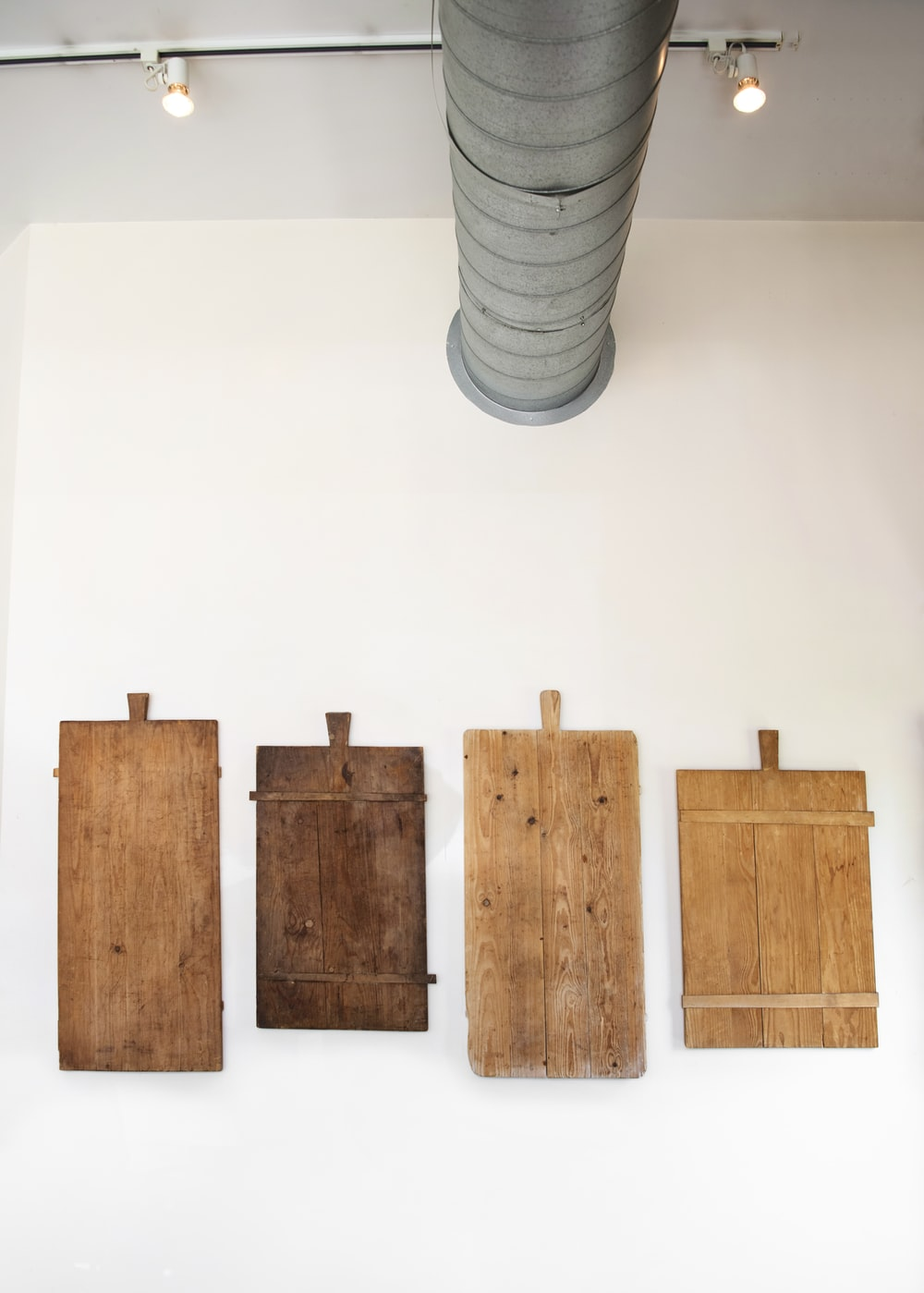 four rectangular brown boards on white wall