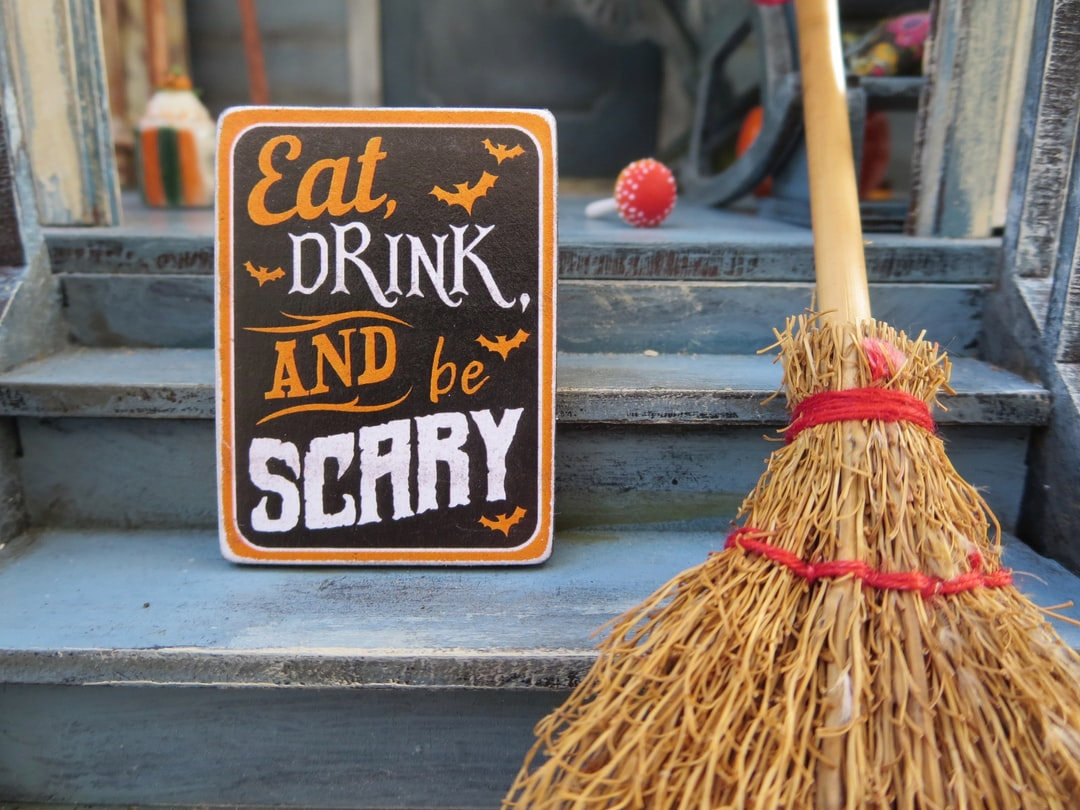 Sign that says eat, drink and be scary next to a broom
